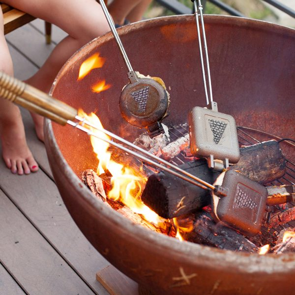 Friends cooking with pie iron in fire pit