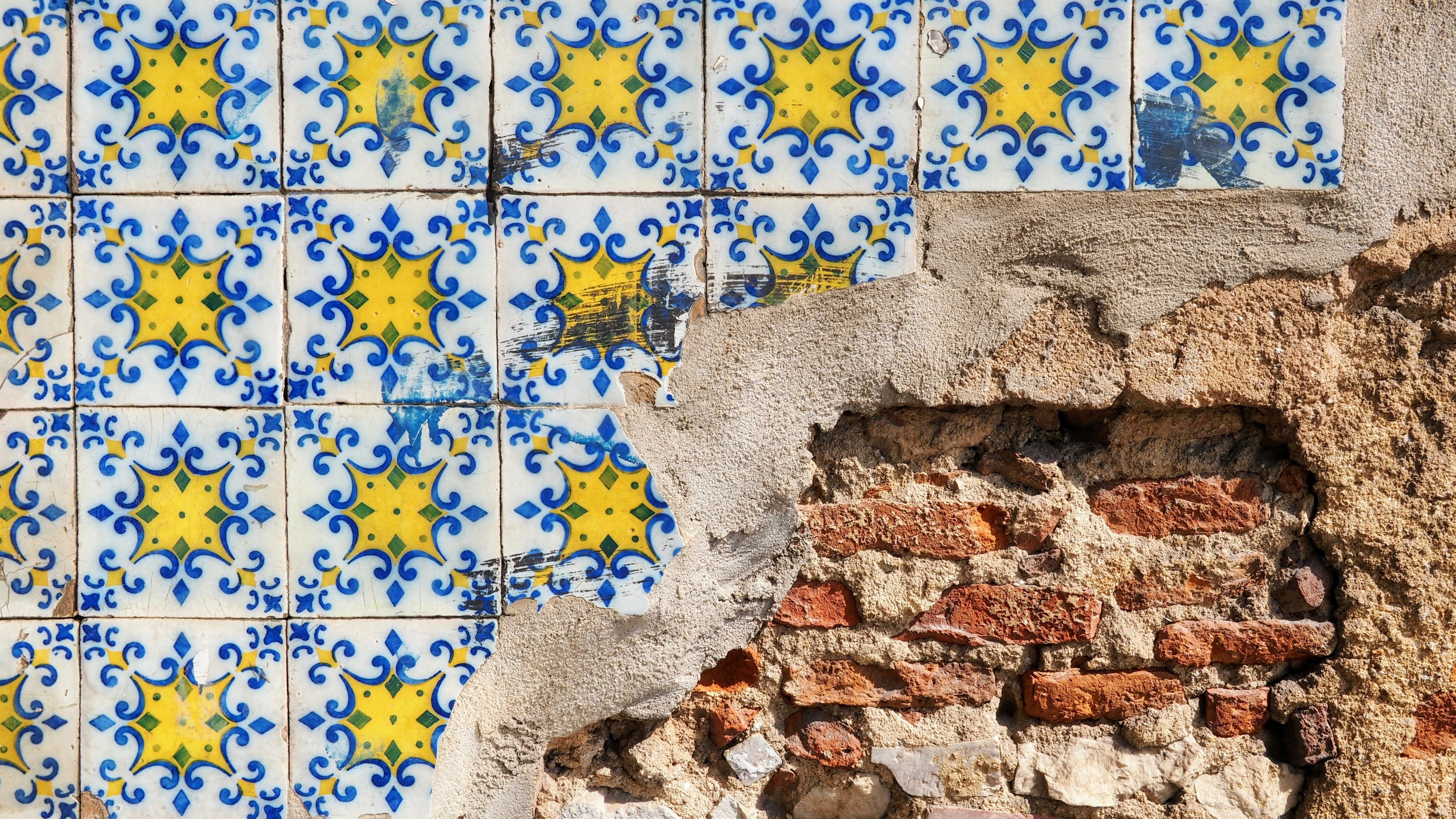 yellow and blue tile wall with exposed brick